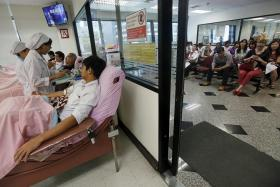 COMPASSION: (Above) Volunteers donating blood at the Thai Red Cross National Blood Centre in Bangkok yesterday. A girl placing flowers at the Erawan Shrine, which reopened yesterday.