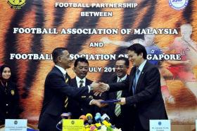 FLASHBACK: FAS general secretary Winston Lee (right) and his FAM counterpart Datuk Azzudin Ahmad exchanging documents in 2011 to finalise the LionsXII's participation in the MSL from 2012, as FAM deputy president Tengku Abdullah Ahmad Shah (second from left) and FAS president Zainudin Nordin look on.