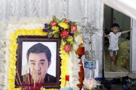 LEFT BEHIND: Lee Jian Han, 6, standing near his father Lee Tze Siang's coffin at his home in Butterworth in Penang.
