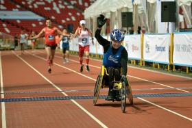 UP FOR IT: Paralympic athlete Dr William Tan at the finishing line of The Straits Times Run at the Sports Hub last year.