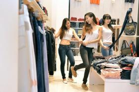 DREAM DENIM: (From left) Ophelia Oliveiro, Stacey Manoharan and Joeypink Lai try on jeans at Levi's Lady's at 313@Somerset.