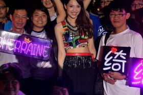 POPULAR: Getai singer Sherraine Law with fans carrying placards spelling out her name in lights at her performance at a getai event at Sin Ming Lane on Wednesday.