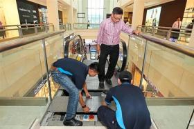CHECKS: Malaysian Lift and Escalator Association president Franky Ho (in pink) inspecting an escalator in a mall in Kuala Lumpur.