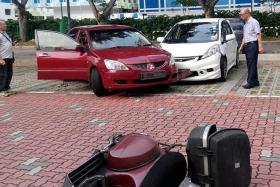 WHAT A MESS: The damaged vehicles left in the wake of the accident. Mr Chng Chor Choo's car is the red Mitsubishi Lancer.