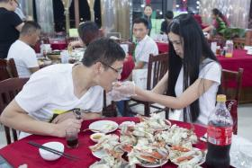 Former air stewardess Xie feeds her customer Feng after he hired her to be his personal crab peeler at RMB10 per crab.