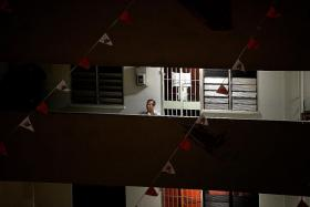 UNHAPPY: (Above) On Thursday, Mr Lim Teck Choon sat outside his former flat for hours until 3am. He spent the rest of the night loitering around the market below the flat. He returned to his rental flat the next day.