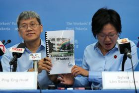 Mr Png Eng Huat (left) and Ms Sylvia Lim holding up the FY 2014/2015 financial report for Aljunied-Hougang-Punggol East Town Council.