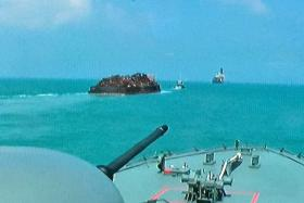 The RSS Resilience (foreground) escorting Permata 1 (centre) to Singapore waters following the successful disruption of the sea robbery.
