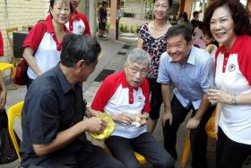 WORKING THE GROUND: Mr Sitoh Yih Pin (above, second from right) sharing a light-hearted moment with Mr Chiam See Tong (second from left) after they met up over pancakes and coffee during their walkabouts on Aug 2. Beside them is Mrs Lina Chiam (right).