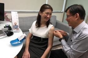 PREVENTIVE MEASURE: Dr Leong Hoe Nam vaccinating patient Ms Teo Guat Kim against pneumonia.