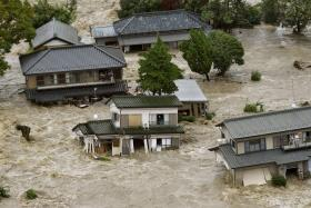 Residents are seen as they wait for rescue helicopters at a residential area flooded by the Kinugawa river, caused by typhoon Etau, in Joso, Ibaraki prefecture.