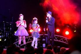 SHOWTIME: Toh En Hui, 13, and her sister Toh Xin Hui, 9, on stage with getai veteran Wang Lei.