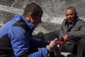 US President Barack Obama is presented with a half-eaten wild salmon by UK survivalist Bear Grylls.