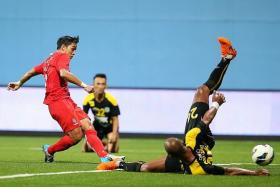 HE'S EVERYWHERE: Hafiz Abu Sujad (in red) shooting at goal in a 2-1 win over Perak in July. The left back is the LionsXII's second highest scorer in the Malaysian Super League with five goals.