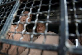 Myanmar nationals Win Zaw Tun (L) and Zaw Lin look out from a prison transport van. They are accused of murdering 24-year-old David Miller and of the rape and murder of Hannah Witheridge, 23, on the southern island of Koh Tao, Thailand.