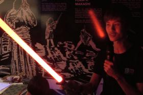 Local lightsaber maker Mr Jay Chen demonstrates how to operate a lightsaber made by Singapore-based company SaberMach.