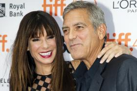 Actress Sandra Bullock and producer George Clooney arrive for the premiere of Our Brand Is Crisis at the Toronto International Film Festival (TIFF)