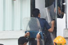 Police armed with riot shields entering the semi-detached house at Paya Lebar Crescent, where a woman known only as Ms Chng and her three children lived. The incident took place in 2013 after what began as a rent dispute turned violent.