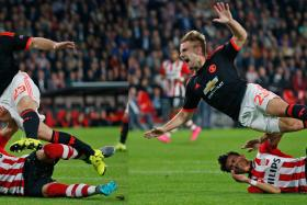 Manchester United's Luke Shaw goes down injured after this challenge from PSV's Hector Moreno