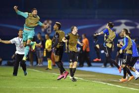 RIDING HIGH: Olympiakos players couldn't hide their joy after their giantkilling act, despite Arsenal's Theo Walcott pulling a late goal back.