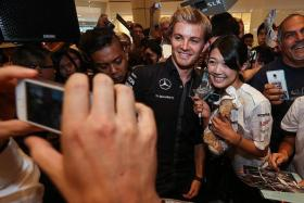 ALL SMILES: Mercedes driver Nico Rosberg (left), with Japanese fan Mana Sugiyama, 19, at a Mercedes-Benz event at Suntec City yesterday.