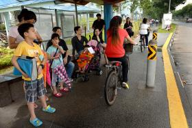 TIGHT FIT: Cyclists and commuters at a bus stop along Woodlands Avenue 9.