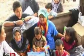 The family receiving some school items collected by the Peninsular Malaysia Malay Students Union Pahang. Intan Maisarah Zulliazam (second from the left) helps out with her family by working at a charcoal kiln after school every day.
