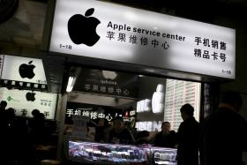 Customers and salespersons are seen at an Apple maintenance service store at a mobile phone market in Shanghai, in this January 24, 2013 file photo. Apple Inc said on Sunday it is cleaning up its iOS App Store to remove malicious iPhone and iPad programs identified in the first large-scale attack on the popular mobile software outlet.