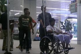 IN HOSPITAL: A man who was speaking to the injured workers at the scene was seen pushing a man in a wheelchair into the A&E unit at Khoo Teck Puat Hospital later that afternoon.