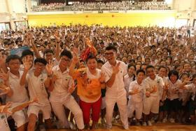 ROLE MODEL NOW: Director Royston Tan (front, right) and getai singer Liu Ling Ling with the students of Zhonghua Secondary School yesterday.