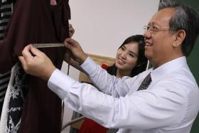 EXPERIMENT: Ms Yvonne Tan, founder of local fashion site Ministry of Retail, showing the ropes to her 'intern' Mr Mok Tuck Seng, a semi-retired business coach.