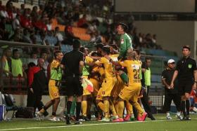 AT THE DEATH: Brunei DPMM (in yellow) celebrating their injury-time winner against Courts Young Lions last night.