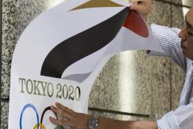 An employee takes down a placard with the Tokyo 2020 Olympic Games emblem during a media event