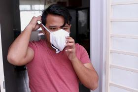 FAN POWER: Mr Mohd Taufiq, 28, went to his Residents' Committee to collect two N95 masks for his mother and himself.