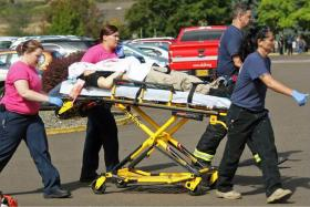 Authorities move a shooting victim after a gunman opened fire at Umpqua Community College in Roseburg, Oregon, on October 1, 2015.