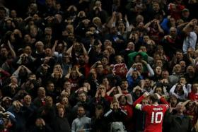 GOOD AND BAD: The Old Trafford fans showing their frustration at another poor Wayne Rooney (above) display but the form of Juan Mata is one of the reasons they are top of the English Premiership.