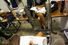 MULTI-TASKING: Student Jessica Goh, 15, getting her hair done as she studies for her exam.