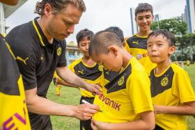 HE'S THE MAN: Lars Ricken (in black) credits Dortmund's revival to coach Thomas Tuchel's ability to instil purpose and conviction.