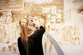 TALENTED: Mrs Maria Filatova-Chan working on a wall mural illustrating contemporary coffee culture in Singapore. The mural is featured at the Coffee Art and Appreciation Exhibition at Temasek Polytechnic.