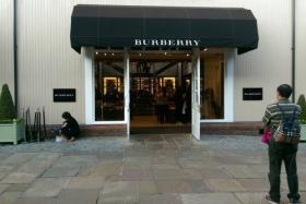An elderly lady is seen holding up a boy while he defecates onto a paper bag right outside of a Burberry outlet in Oxfordshire, England.