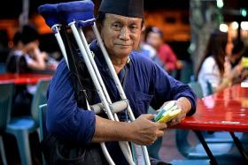 HARD WORK: (Above) Mr Mohd Isa Saat sells tissue packs at eateries in Bedok.
