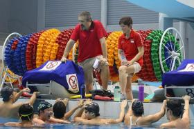 LEADING THE CHARGE: Sonya Porter (right) and national swimming coach Sergio Lopez chatting with national swimmers at the OCBC Aquatic Centre.