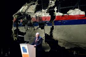FINDING ANSWERS: Dutch Safety Board Chairman Tjibbe Joustra speaking in front of the reconstructed wreckage of the Malaysia Airlines Boeing 777.