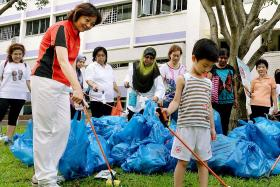 PARTICIPATION: Nee Soon residents (above) at a litter-picking exercise. Ms Lee Bee Wah (in red) thinks rewarding those who report litterbugs will create a sense of participation among residents.