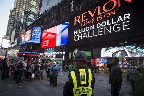 ON ALERT: A public safety officer keeps watch as people take pictures in front of Revlon's 'Kiss Cam' billboard in New York's Times Square.