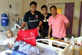 TOUCHING GESTURE: LionsXII team manager Farehan Hussein, with midfielder Zulfahmi Arifin and coach Fandi Ahmad, handing over the signed jersey to Norruzainal Norhisham, who is battling lymphoma.