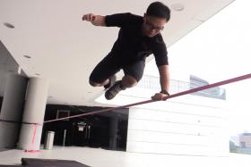 TRICKS: Mr Heng Yongli performing tricklining, which involves stunts such as bouncing, somersaults and backflips.