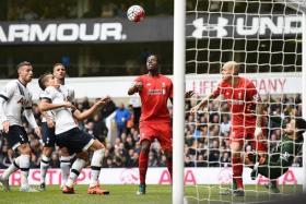 SHOT AT GOAL: Liverpool's Divock Origi (centre) watches his effort come back off the crossbar.