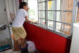 SCARED: Madam Zahirah Mohamed Sultan showing how she climbed out her kitchen window after her boyfriend broke into her flat.