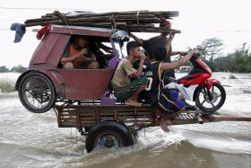 MAKING DO: A motorised tricycle and residents hitch a ride on a tractor trailer along a flooded highway in Zaragoza, northern Phillipines.